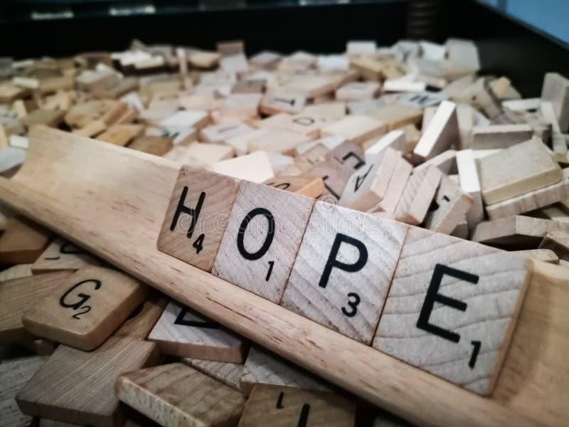Hölzernes Quadrat deckt die Buchstaben mit Ziegeln, die formulieren das Wort ` Hoffnung ` stockbild