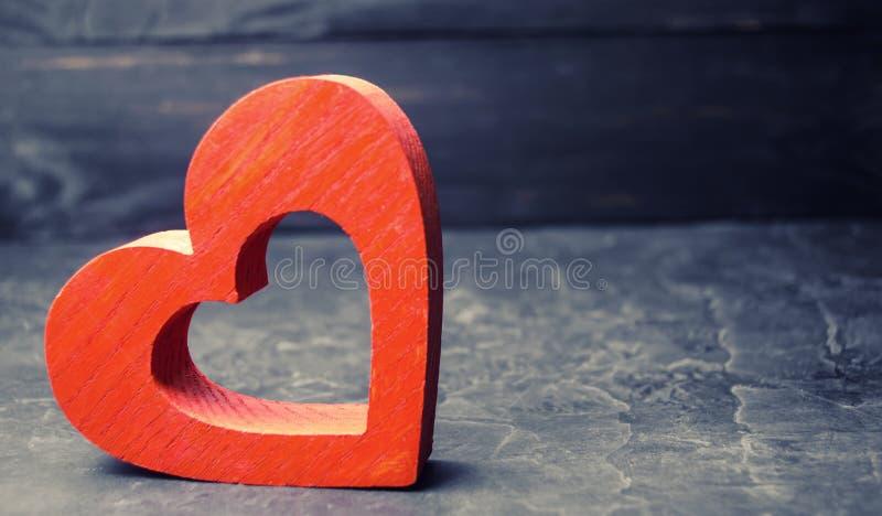 Hölzernes rotes Herz auf einem schwarzen Hintergrund Konzept der Liebe und Romantik Getrennt auf Weiß Organspende Das Verhältnis  lizenzfreies stockbild
