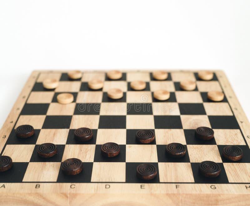 Hölzernes Schachbrett mit den Kontrolleuren gesperrt lokalisiert auf Weiß lizenzfreie stockfotografie