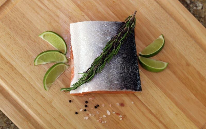Hölzernes Schneidebrett im Küchentisch mit frischen roten Lachsen fischen Salzpfeffer und kalken kochfertiges stockfotos