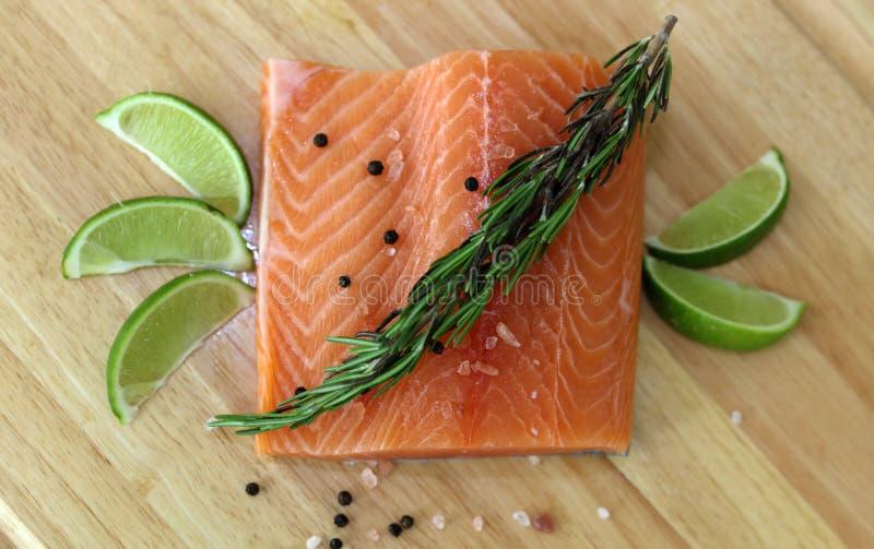 Hölzernes Schneidebrett im Küchentisch mit frischen roten Lachsen fischen Salzpfeffer und kalken kochfertiges lizenzfreie stockfotos