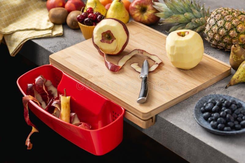 Hölzernes Schneidebrett mit Abfallbehälter, Santoku-Chef Knife und frischen Früchten lizenzfreie stockfotografie