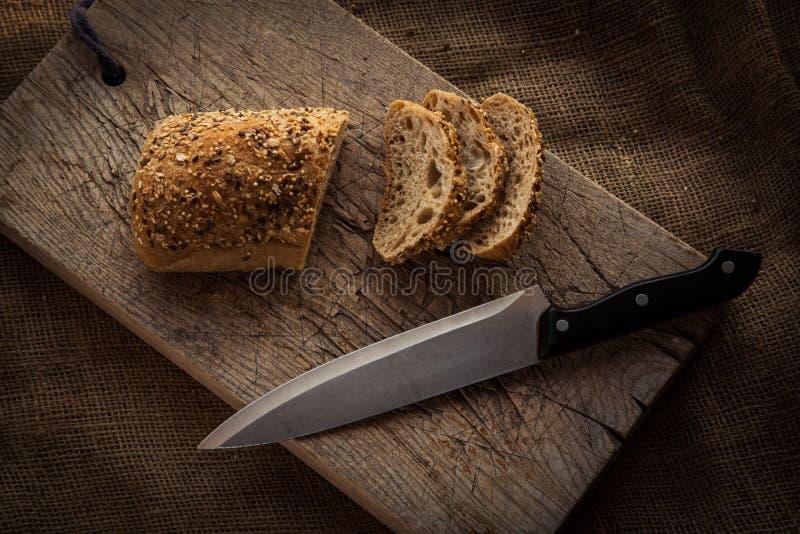 Hölzernes Schneidebrett mit geschnittenem Brot stockfoto