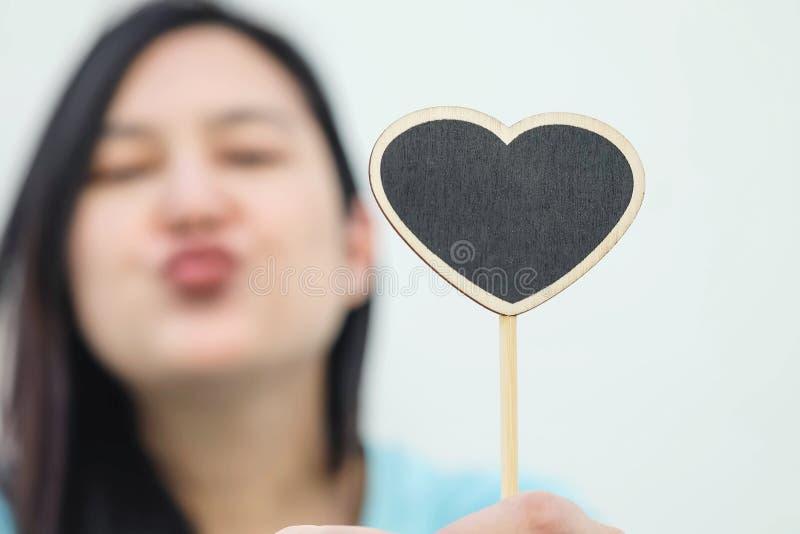 Hölzernes schwarzes Brett der Nahaufnahme in der Herzform mit verwischt senden ein Kussgesicht des Frauenhintergrundes lizenzfreie stockfotos