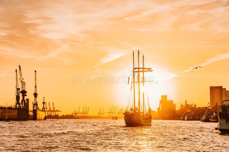 Hölzernes Segelbootsegeln in Richtung zum drastischen Sonnenuntergang, der neues Reiseabenteuer mit Fliegenvogel anfängt stockfotos