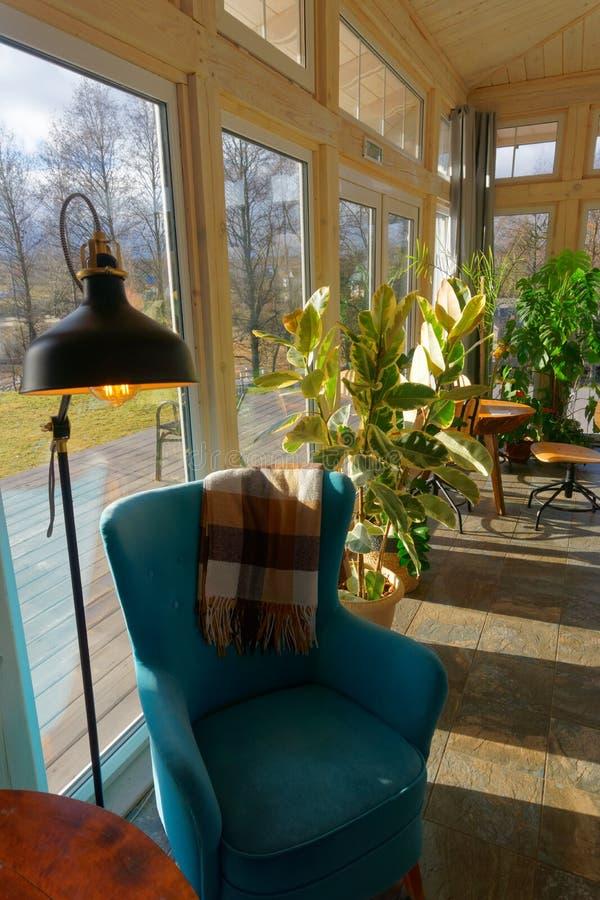 Hölzernes sonniges sundeck im Herbst mit blauem Lehnsessel und Grünpflanzen lizenzfreie stockfotografie