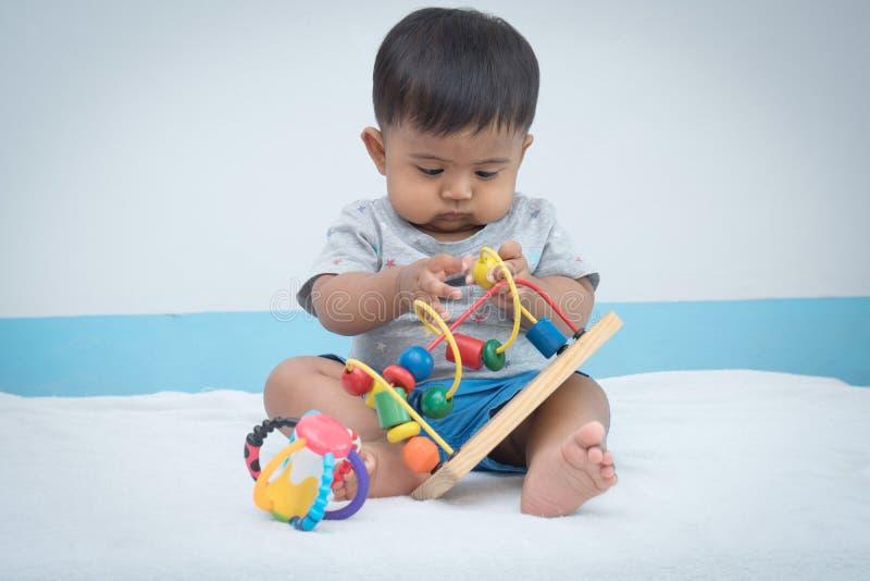 hölzernes Spielzeug des wenig asiatischen Babyspiels stockfotografie