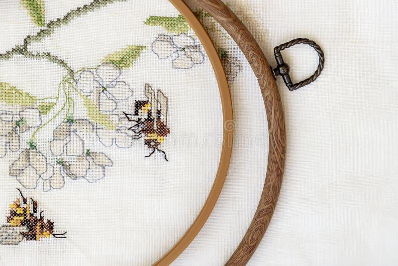 Hölzernes Stickereiband mit Fragment einer bunten Kreuzstichstickerei, Sommerblumenverzierung Beschneidungspfad eingeschlossen lizenzfreie stockfotos