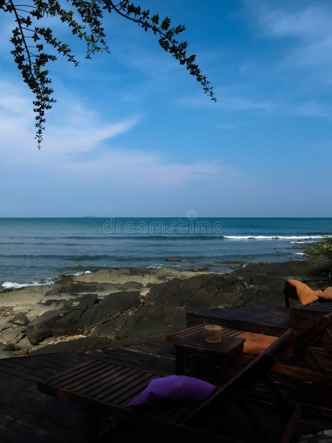 Hölzernes Strandbett auf dem Strand mit Felsen und blauem Himmel stockbilder