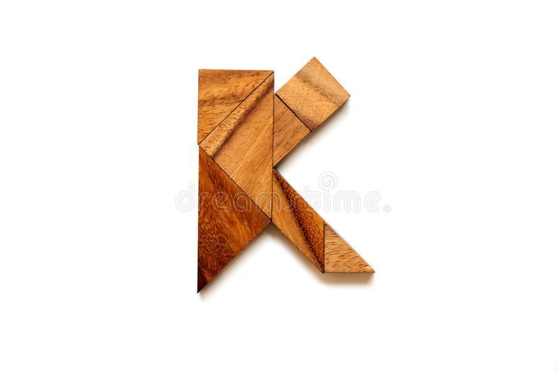 Hölzernes Tangrampuzzlespiel als Buchstabe K des englischen Alphabetes stockfotos