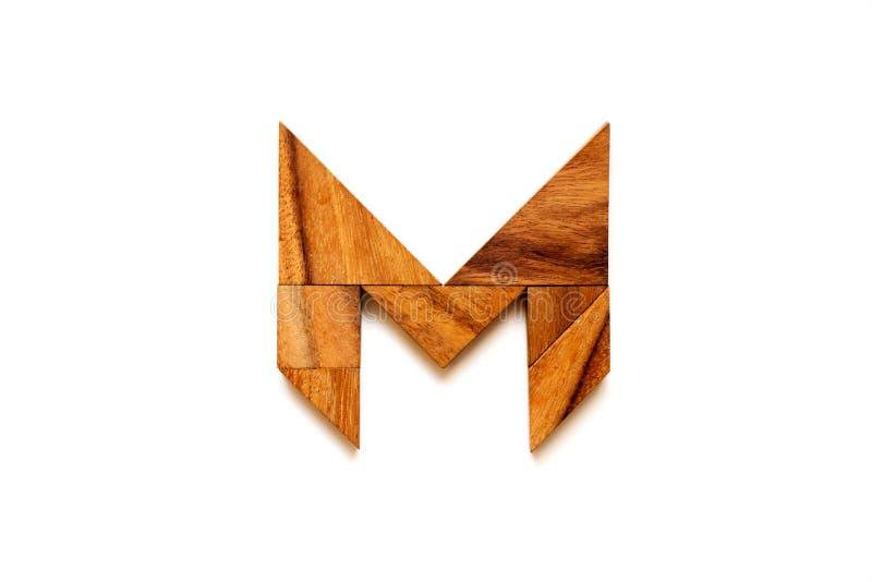 Hölzernes Tangrampuzzlespiel als Buchstabe M des englischen Alphabetes stockfotos