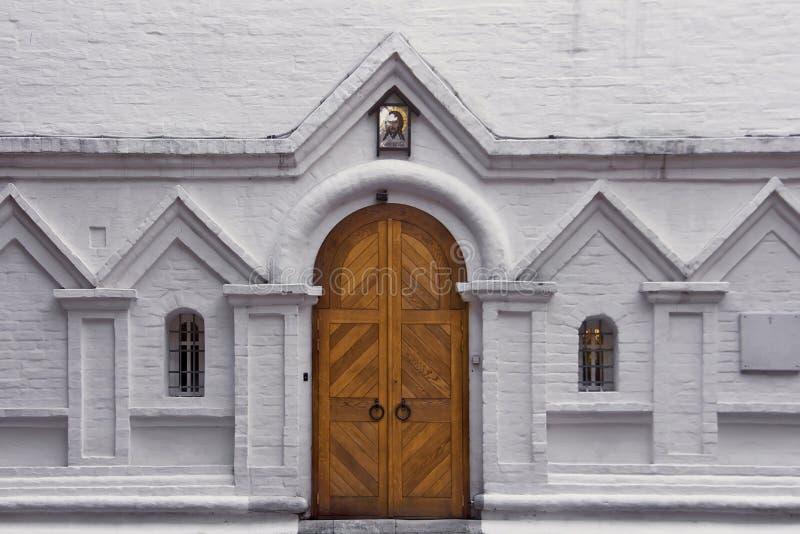 Hölzernes Tor und zwei gewölbte Fenster auf einer weißen Backsteinmauer Eingang zur alten christlichen Kirche lizenzfreie stockbilder