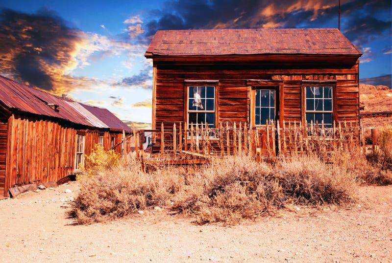 Hölzernes verlassenes Haus in der Wüste bei Sonnenuntergang stockfotografie