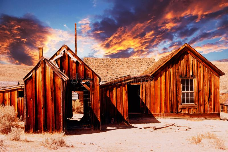 Hölzernes verlassenes Haus in der Wüste bei Sonnenuntergang stockbild