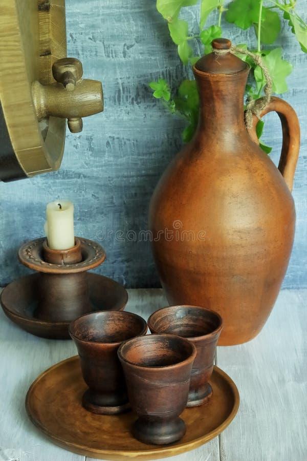 Hölzernes Weinfaß, keramischer Krug, Platte mit Lehmschalen und keramischer Kerzenständer mit weißer Kerze auf hölzerner rustikal stockbilder