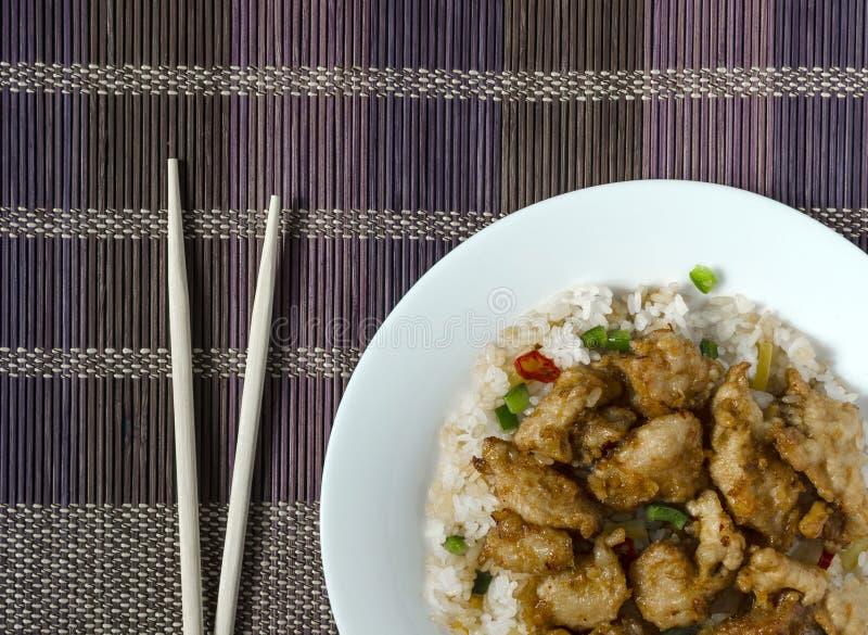 Höna i söt och sur sås och ris med grönsaker på en flerfärgad bakgrund för vita plattaträpinnar royaltyfri bild