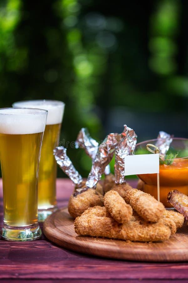 Höna och ost ställde in för öl och två exponeringsglas av öl Fega vingar, ostpinnar och ostbollar med ljust royaltyfri bild