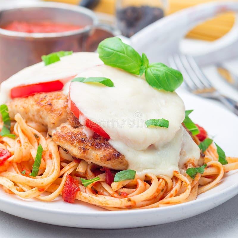 Höna som är caprese med tomat- och mozzarellaost som tjänas som med linguine, tomatpastasås och basilika, fyrkant, closeup royaltyfri fotografi