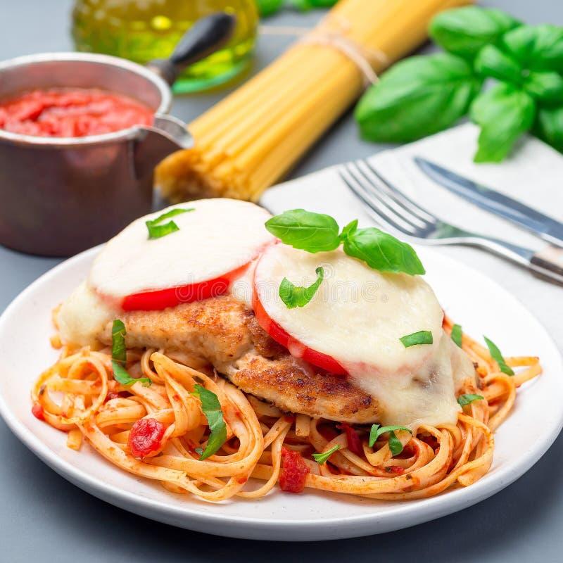 Höna som är caprese med tomat- och mozzarellaost som tjänas som med linguine, tomatpastasås och basilika, fyrkant arkivbild