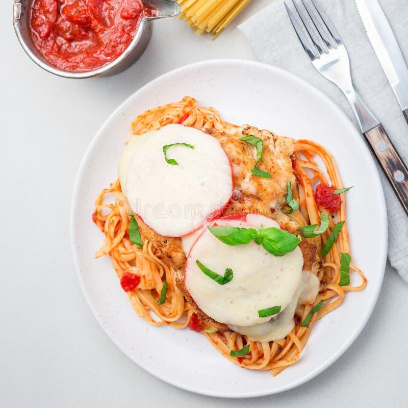 Höna som är caprese med tomat- och mozzarellaost som tjänas som med linguine, tomatpastasås och basilika, fyrkantig bästa sikt fotografering för bildbyråer