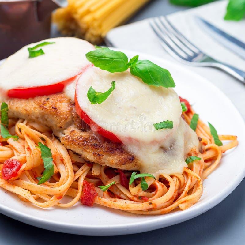 Höna som är caprese med tomat- och mozzarellaost som tjänas som med linguine, tomatpastasås och basilika, fyrkantigt format royaltyfria foton