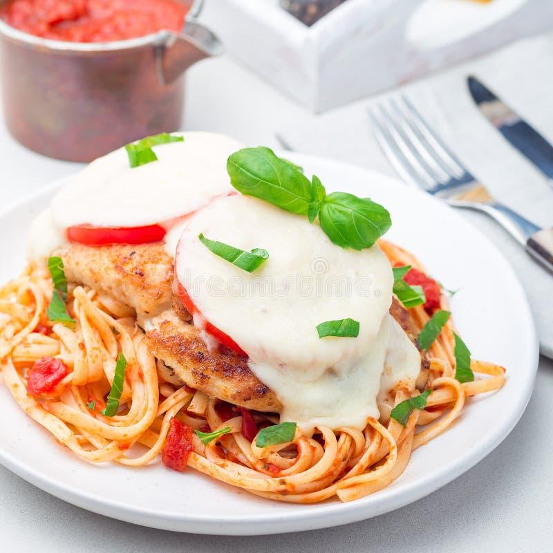 Höna som är caprese med tomat- och mozzarellaost som tjänas som med linguine, tomatpastasås och basilika, fyrkantigt format arkivfoto