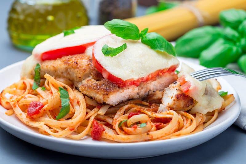 Höna som är caprese med tomat- och mozzarellaost som tjänas som med linguine, tomatpastasås och basilika som är horisontal, close royaltyfri bild