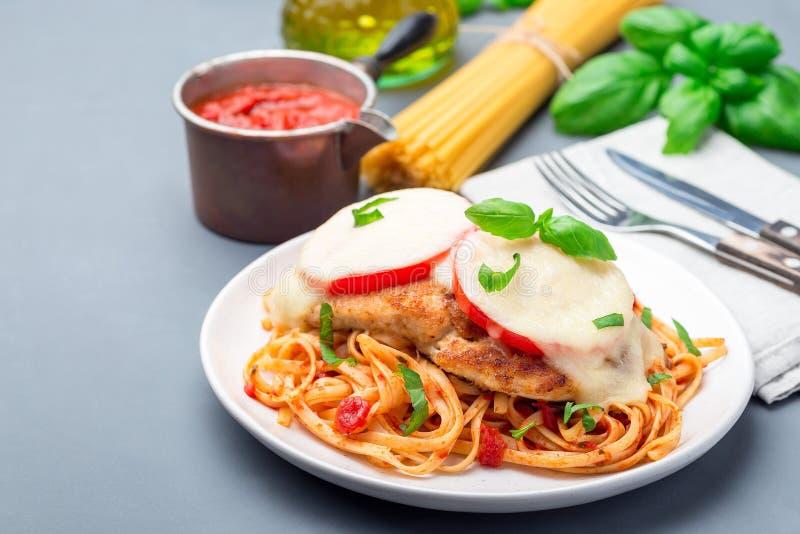 Höna som är caprese med tomat- och mozzarellaost som tjänas som med linguine, tomatpastasås och basilika som är horisontal, kopie arkivbild