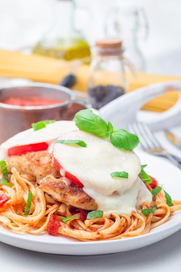 Höna som är caprese med tomat- och mozzarellaost som tjänas som med linguine, tomatpastasås och basilika som är vertikala fotografering för bildbyråer