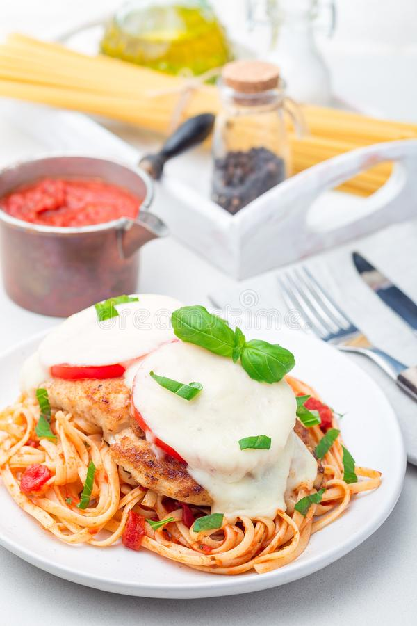 Höna som är caprese med tomat- och mozzarellaost som tjänas som med linguine, tomatpastasås och basilika som är vertikala royaltyfri bild