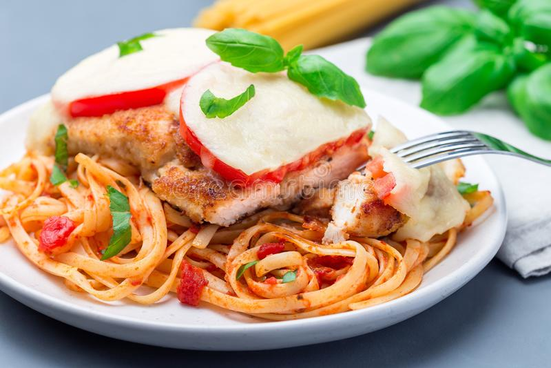 Höna som är caprese med tomat- och mozzarellaost som tjänas som med linguine, tomatsås och basilika som är horisontal, closeup arkivbild