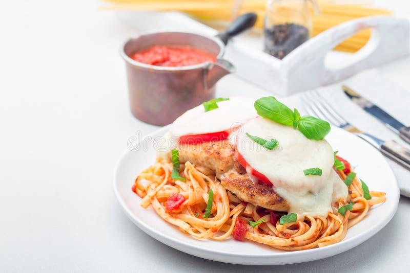 Höna som är caprese med tomat- och mozzarellaost som tjänas som med linguine, tomatsås och basilika som är horisontal, kopierings arkivbild