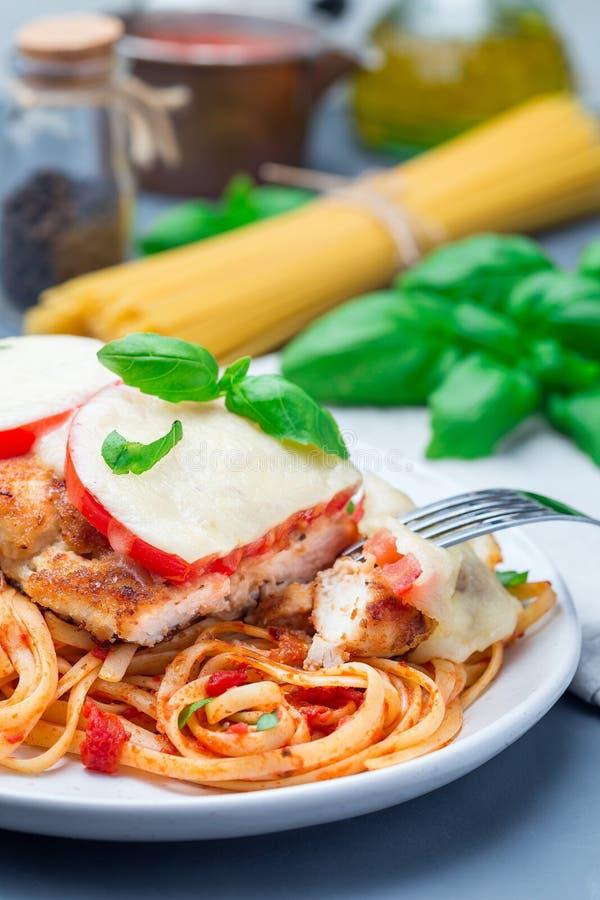 Höna som är caprese med tomat- och mozzarellaost som tjänas som med linguine, tomatsås och basilika som är vertikala arkivfoto