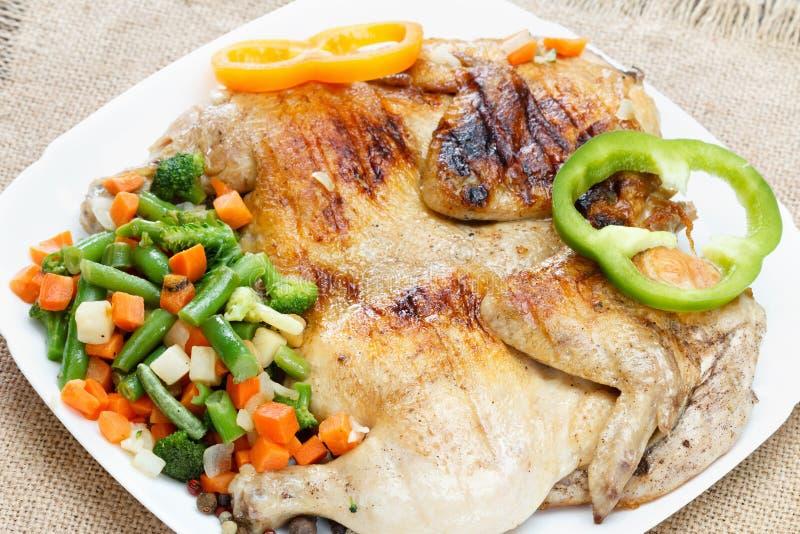 Höna stekte med grönsaker på en servett av säckväv arkivbild