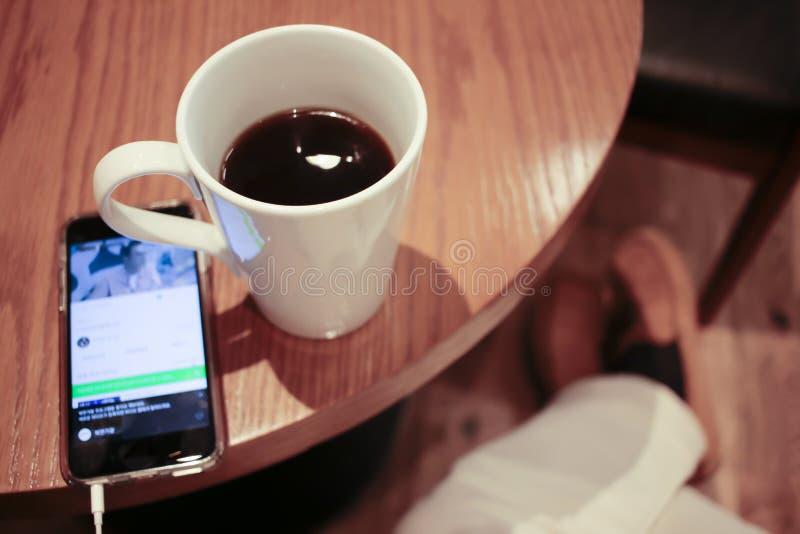 Hören Musik auf einem Smartphone beim Trinken des Kaffees allein in einem Café stockfoto
