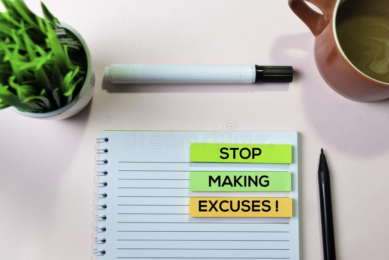 Hören Sie auf, Entschuldigungen zu machen! Text auf klebrigen Anmerkungen mit Schreibtischkonzept stockbild