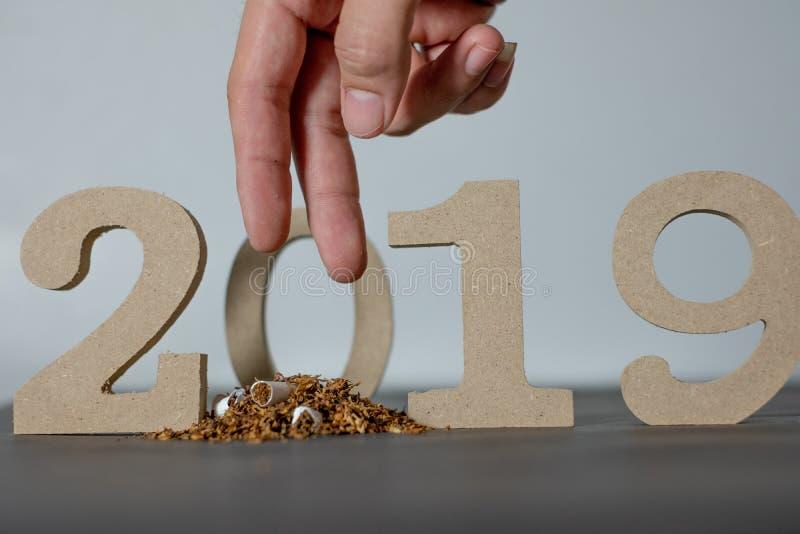 Hören Sie auf, 2019 zu rauchen und Einstellungstag 2019 auf einem schwarzen Hintergrund und Händen rauchen, die Zigaretten zerstö stockbild