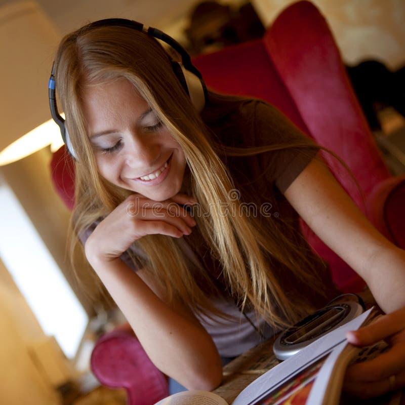 Hörende Musik der Frau in den Kopfhörern stockfotos