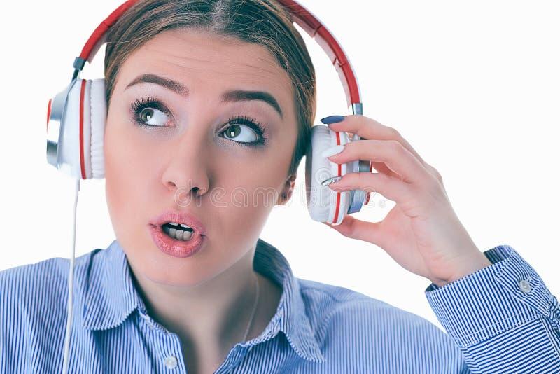 Hörende Musik der Frau mit Kopfhörern von einem intelligenten Telefon und fragt, was? lizenzfreies stockfoto