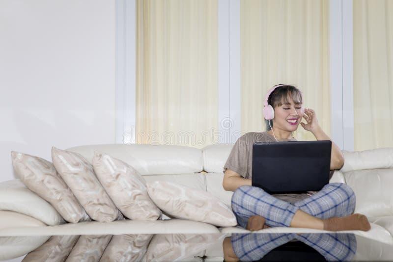 Hörende Musik der glücklichen Frau durch Gebrauch ein Laptop stockfoto
