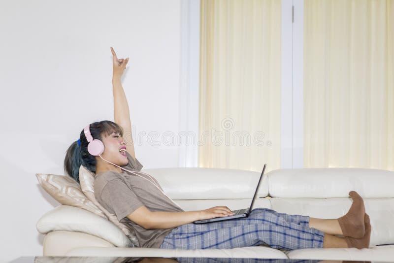 Hörende Musik der glücklichen Frau mit einem Laptop lizenzfreies stockfoto