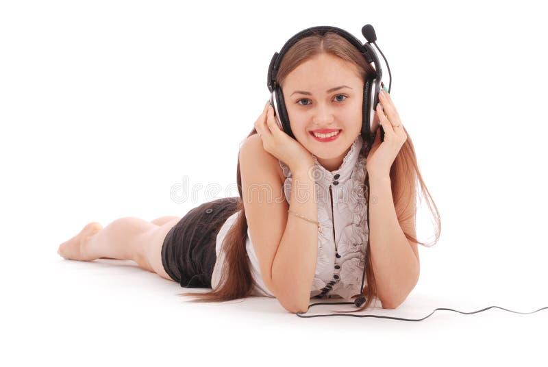 Hörende Musik der hübschen Jugendlichen auf ihren Kopfhörern stockfotografie