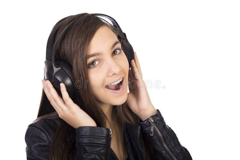 Hörende Musik der hübschen Jugendlichen auf ihren Kopfhörern und singi stockfotografie