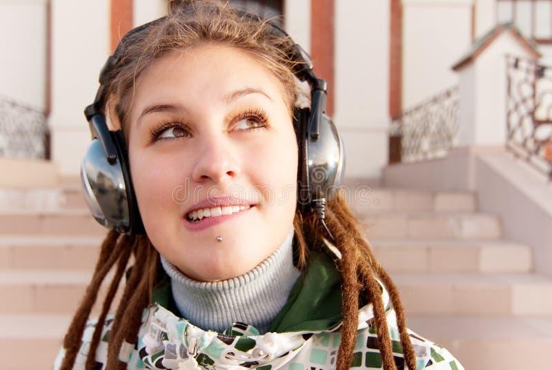 Hörende Musik der jungen Frau stockfotografie
