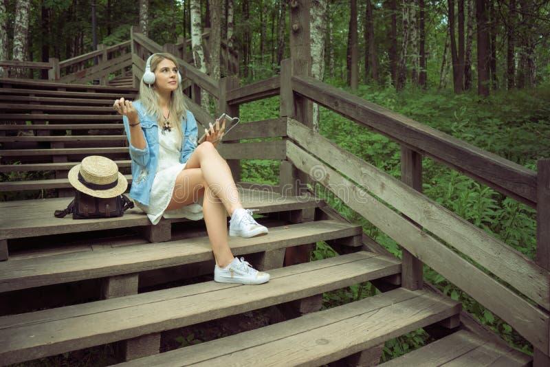 Hörende Musik der schönen jungen blonden Hippie-Frau in den Kopfhörern im Park mit Tablette in den Händen, sitzend auf hölzernen  stockfoto