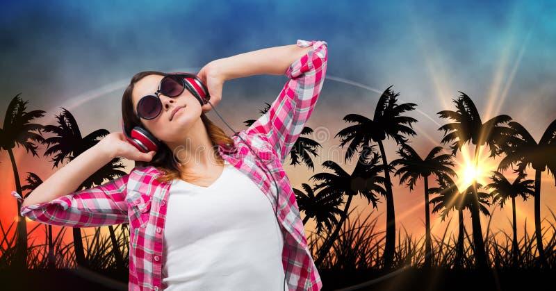 Hörende Musik der Schönheit durch Kopfhörer bei der Stellung gegen Schattenbildbäume stockfotografie