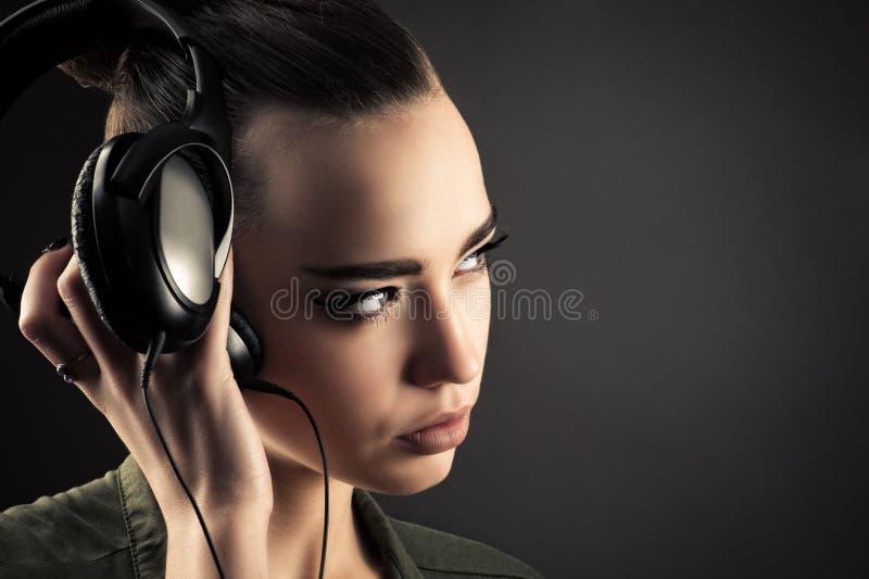 Hörende Musik des attraktiven Mädchens durch Kopfhörer stockfoto