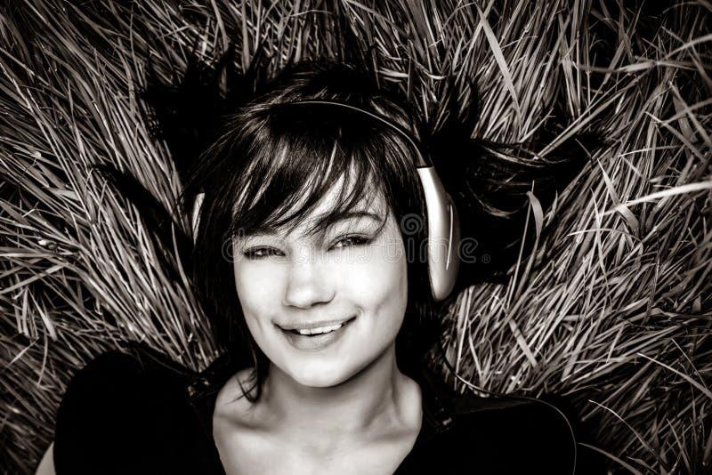 Hörende Musik des Brunettemädchens am Gras stockbild