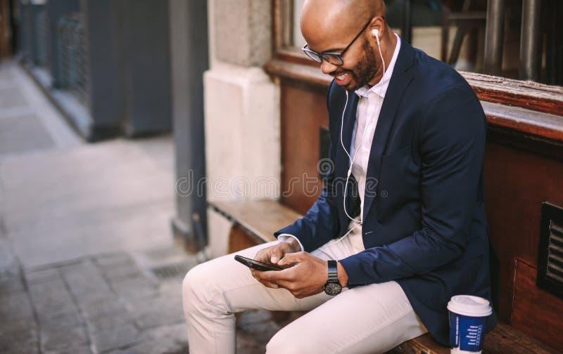 Hörende Musik des glücklichen Geschäftsmannes mit Telefon draußen stockbild