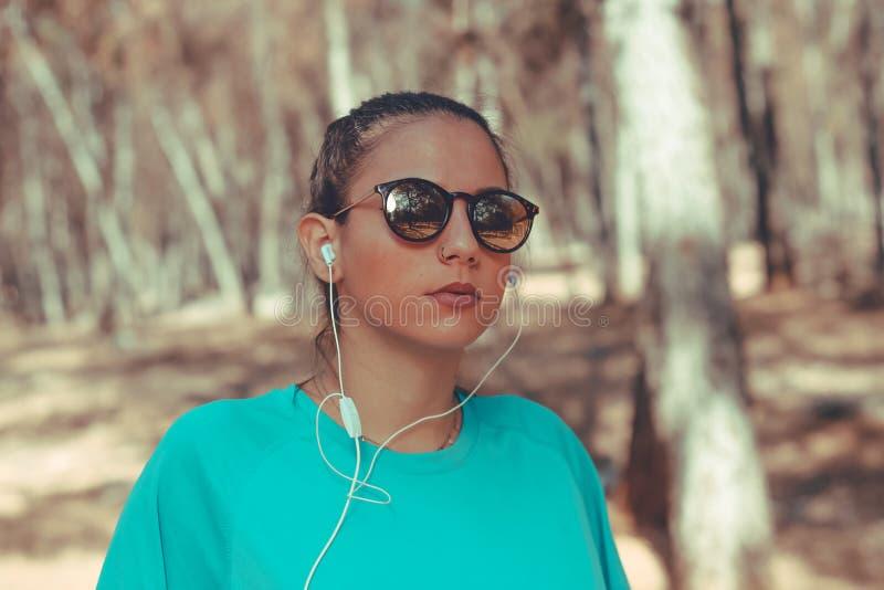 Hörende Musik des jungen Mädchens nach Lauf stockbild
